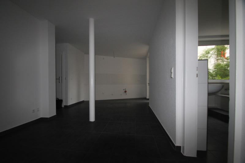 Leerer, weißer Flur mit schwarz gefliestem Boden und einer weißen Säule