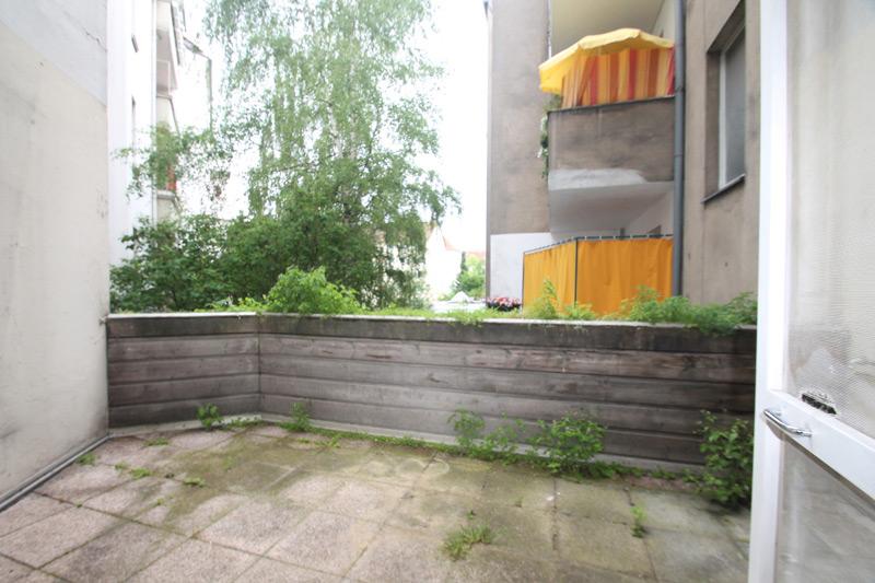 Bewachsener Balkon mit Unkraut zwischen den Steinplatten