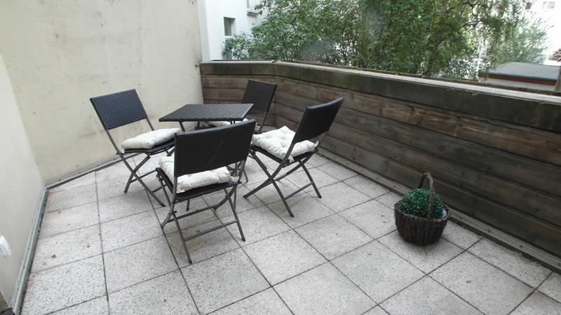 Balkon mit hellen Steinplatten und anthrazitfarbenen Gartenmöbeln