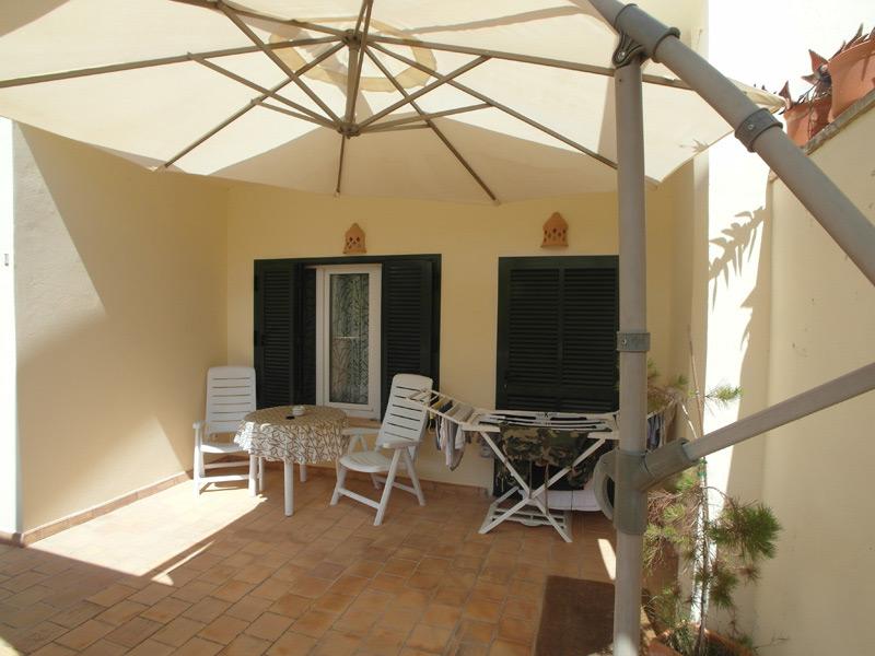 Balkon mit braunen Bodenfliesen und einem großen Sonnenschirm