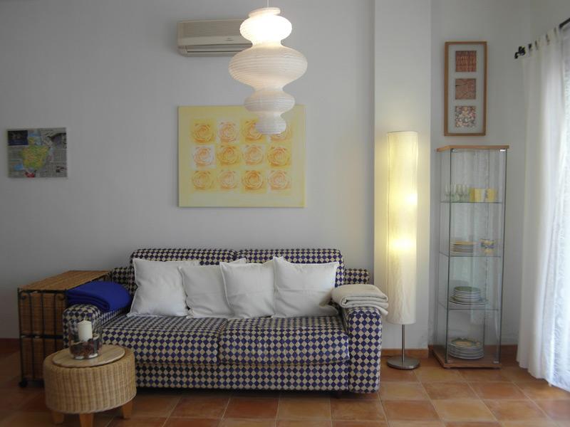 Weißes Wohnzimmer mit brauen Boden und einem Schachbrett-Muster Sofa