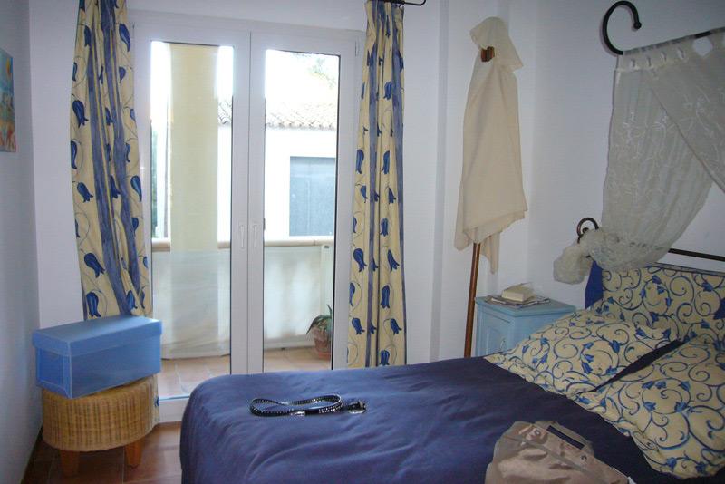 Schlafzimmer mit einem blauen Doppelbett und einem durch eine Fenstertür begehbaren Balkon