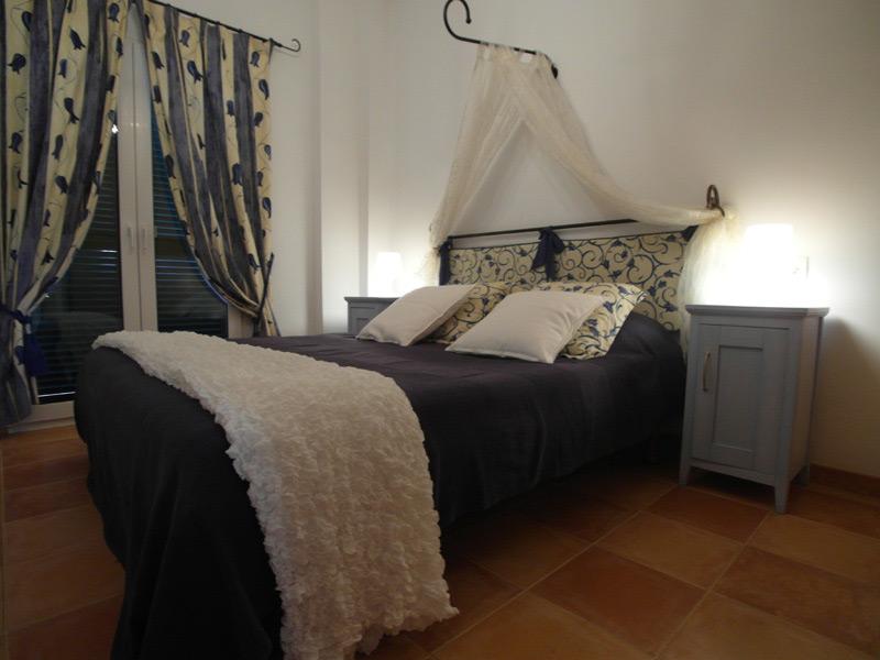 Ein Doppelbett mit einem Vorhang an der Kopfspitze des Bettes