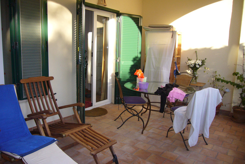 Balkon mit Liegen, sowie einem runden Glastisch und drei Stühlen