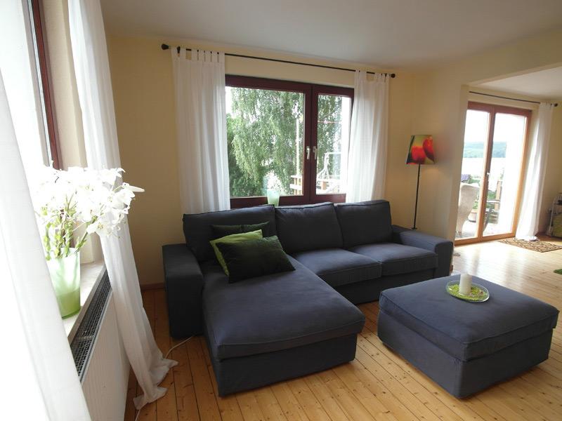 Offenes Wohnzimmer mit viel Tageslicht, einem Holzboden und einer Eckcouch