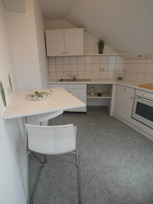 Weiße Küche mit hellgrauem Boden und einem Wandtisch