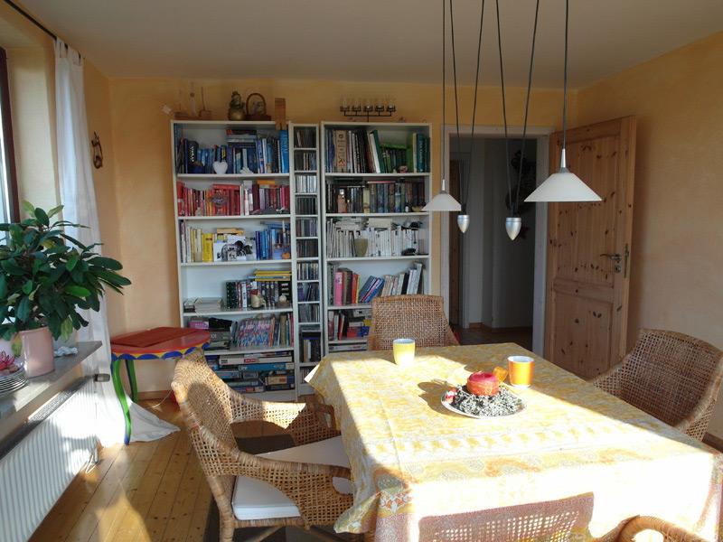 Esszimmer mit zwei vollen Bücherregalen, getrennt durch ein schmales CD-Regal