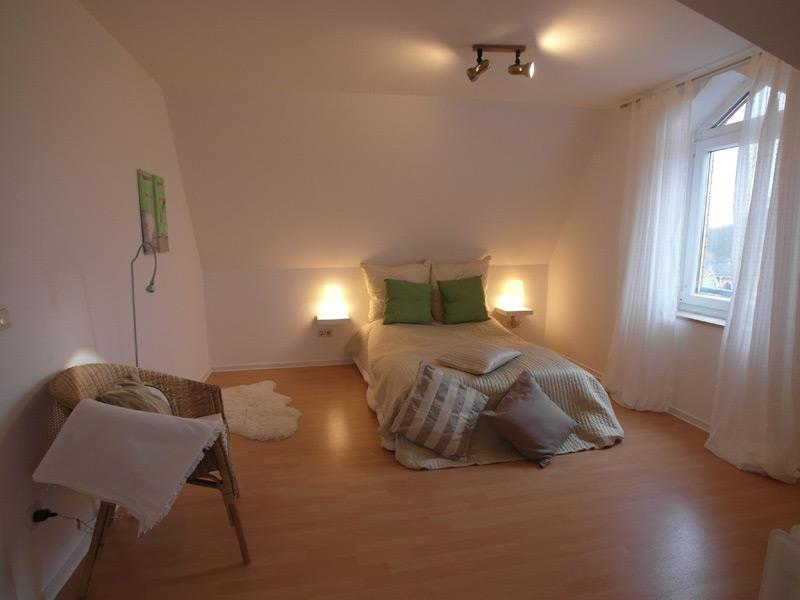 Weißes Schlafzimmer mit warmem Licht und einem Laminatboden