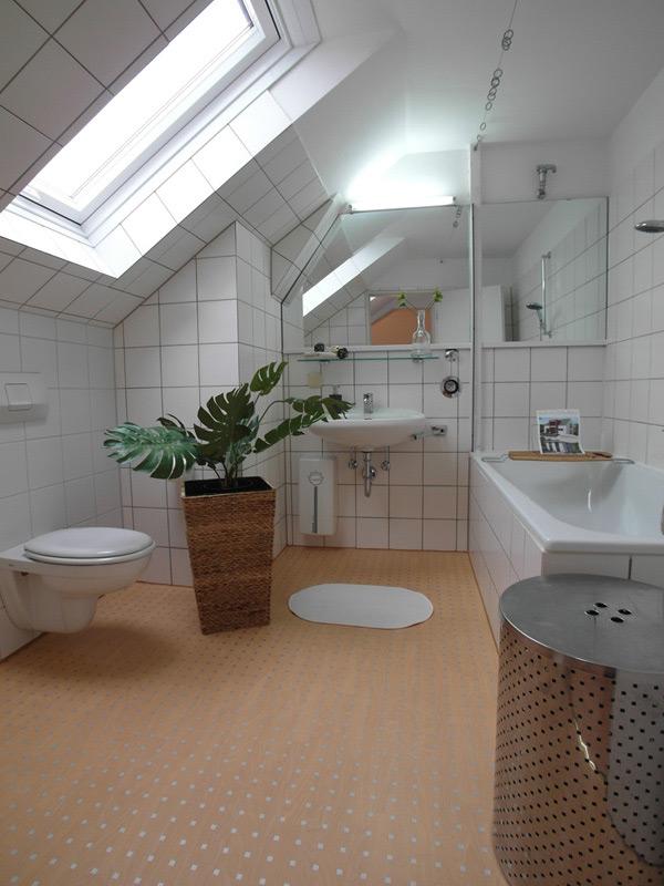 Weißes Badezimmer mit tonfarbenem Teppich und einer Grünpflanze