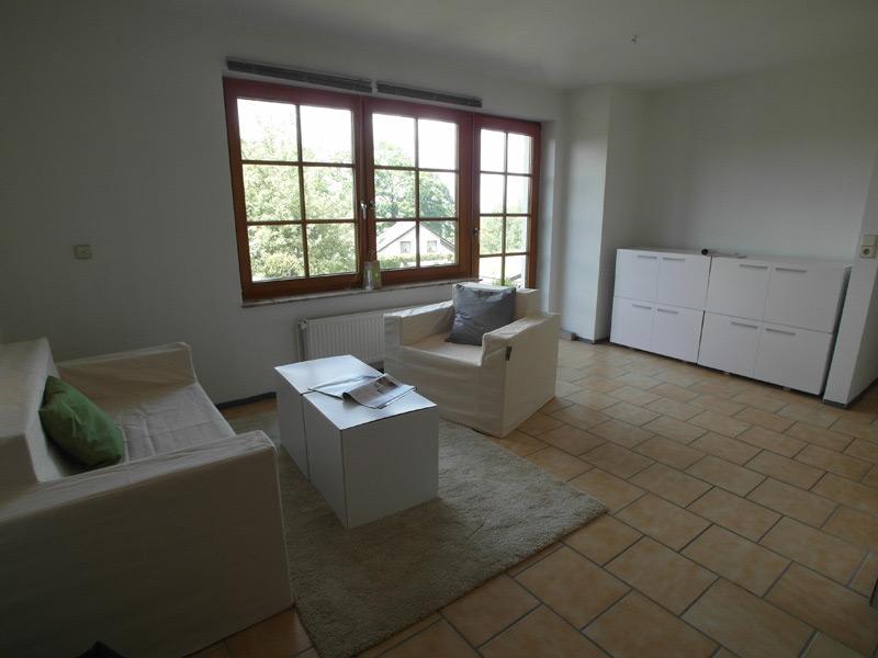 Weißes Wohnzimmer mit beigen Fliesen und weißem Mobiliar