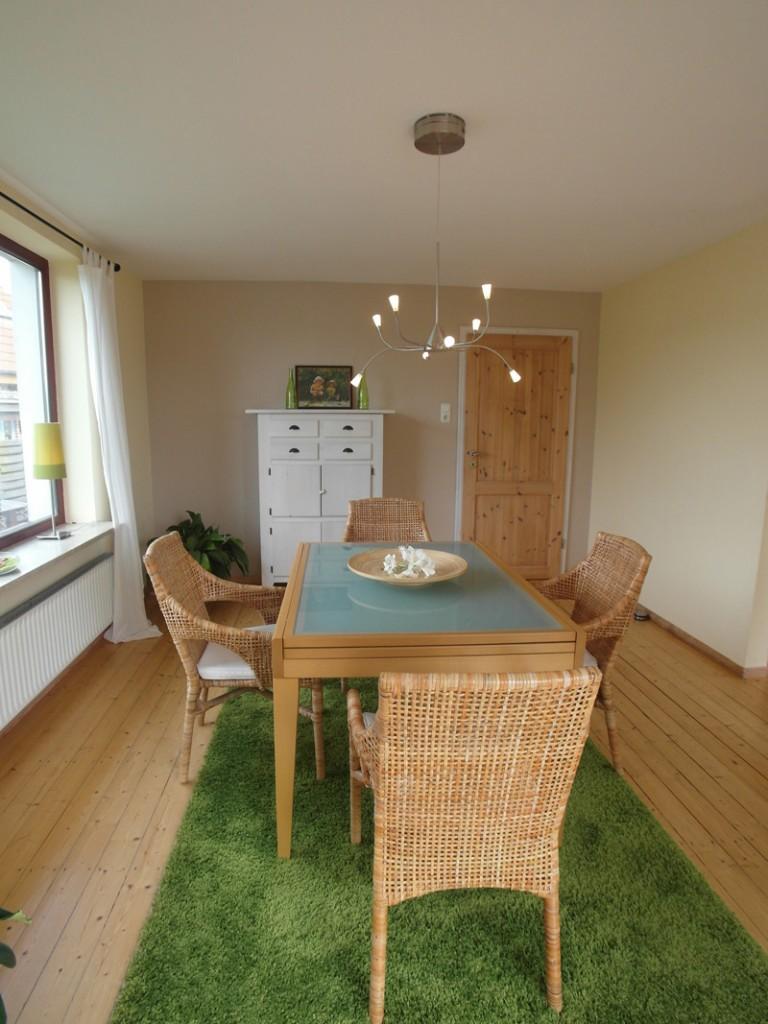 Weißes Esszimmer mit Holzboden und Korbmöbeln auf einem grünen Flusenteppich