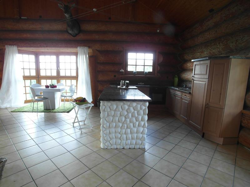 Rustikale Landhaus Küche mit einem weißen Naturstein Tresen und Baumstamm-Wänden