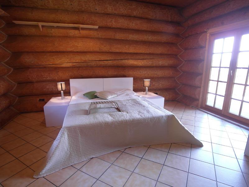 Schlafzimmer in einem Landhaus mit Baumstamm-Wänden