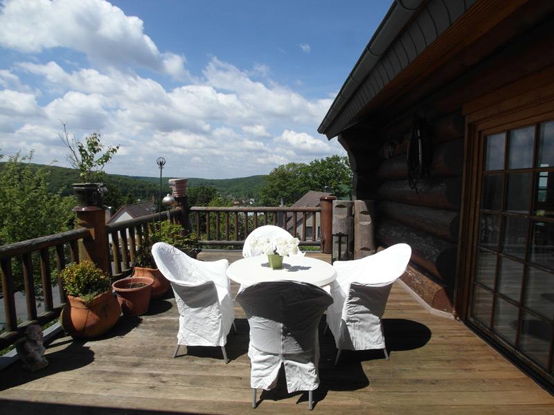 Rustikaler Balkon eines Landhauses mit vier weißen Stühlen um einen runden Tisch