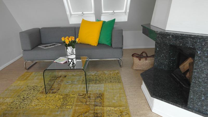Gebogener Glastisch vor einem Marmor-verkleideten Kamin