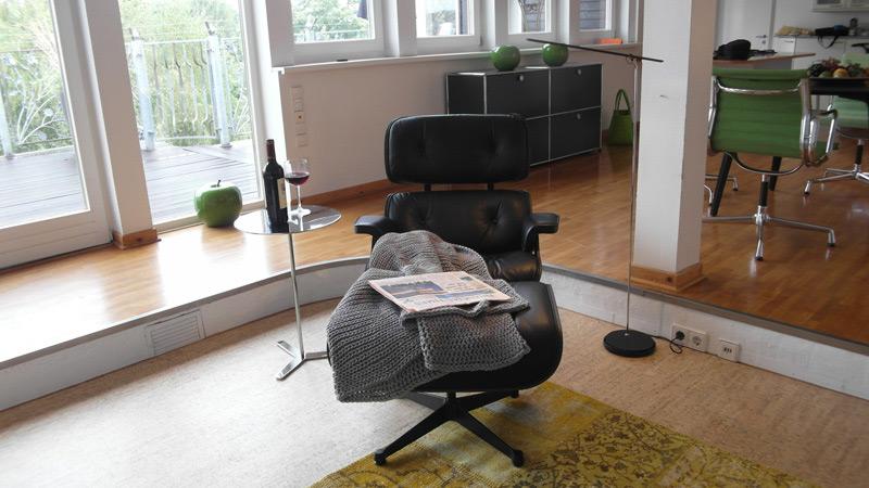 Wohnzimmer Sessel mit einem Beistelltisch auf dem ein Glas Rotwein ruht