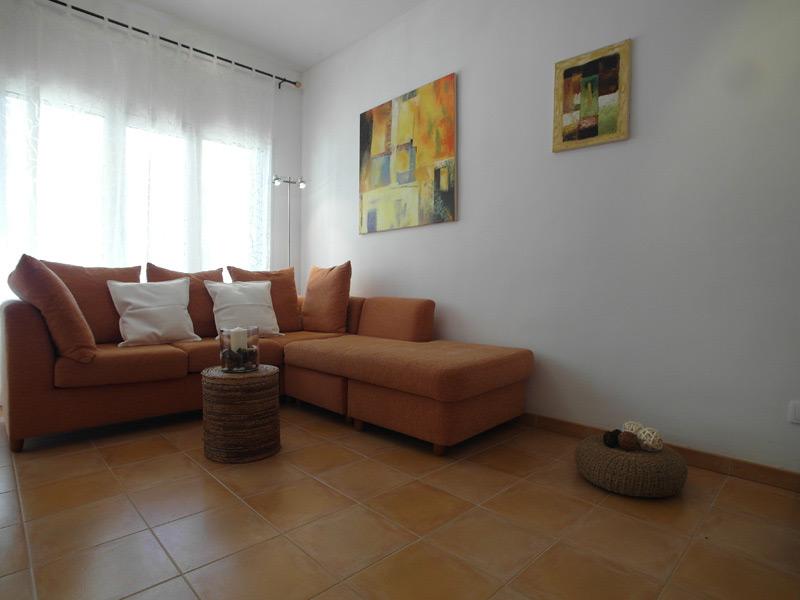 Weißes Wohnzimmer mit rot-braunen Bodenfliesen und einer Tonfarbenen Eckcouch