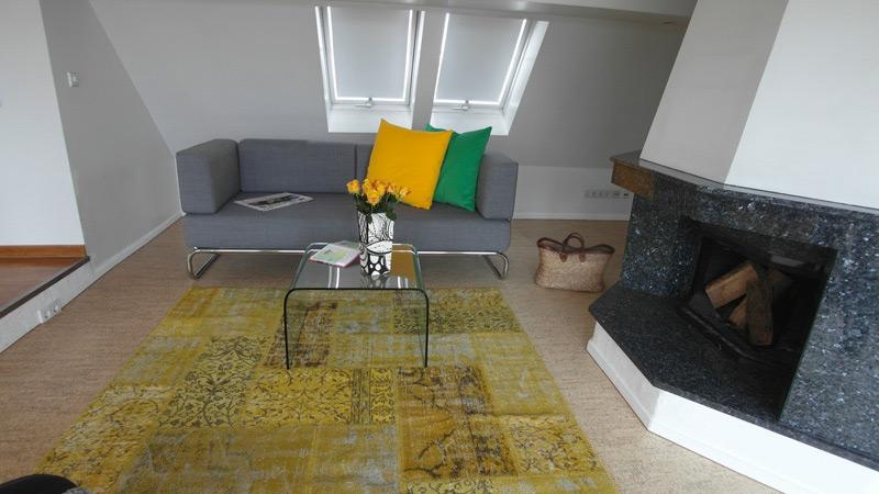 Wohnzimmer mit einem gebogenen Glastisch vor einem Kamin mit Marmor-Verkleidung