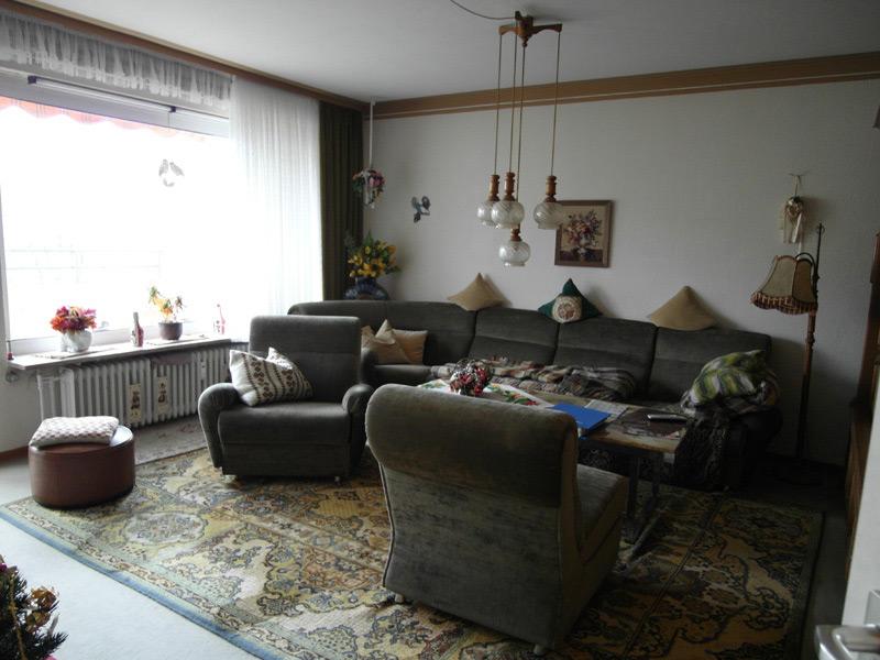 Altmodisches Wohnzimmer mit dunkelgrünem Mobiliar und einem Orientteppich