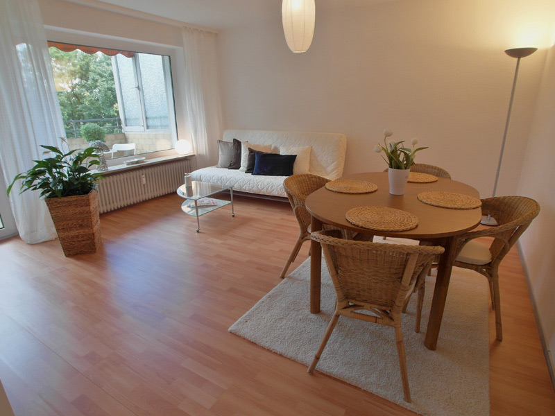 Weißes Wohnzimmer mit Laminatboden, trendy Mobiliar und Dekopflanzen
