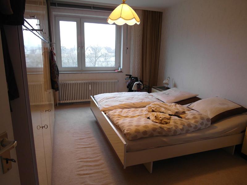 Schlafzimmer mit Doppelbett gegenüber einer Schrankwand