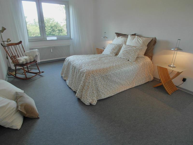 Weißes Schlafzimmer mit grauem Teppichboden und einem Doppelbett, sowie einem Schaukelstuhl