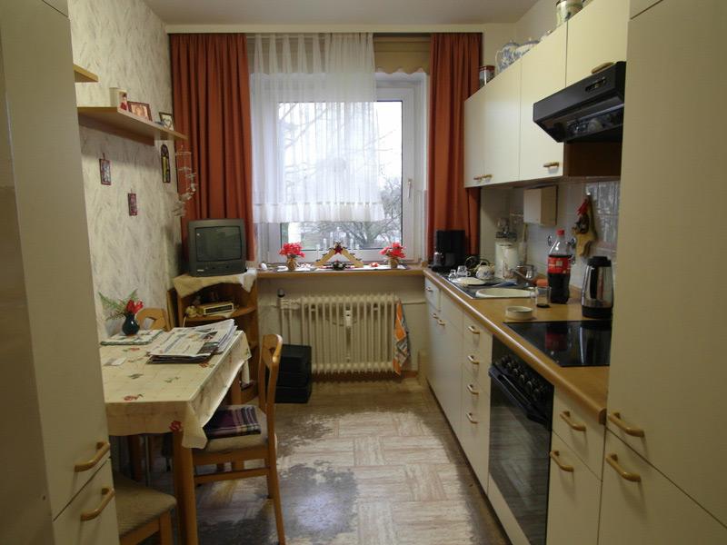 Vollgestellte Küche mit kaputtem Fußboden