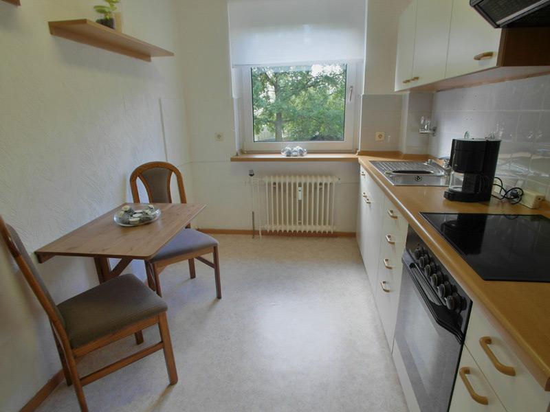 Kleine Küche mit einem Wandtisch und zwei Stühlen