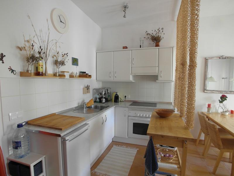 Weiße Küchenzeile mit einem kleinen Holz-Wandregal darüber