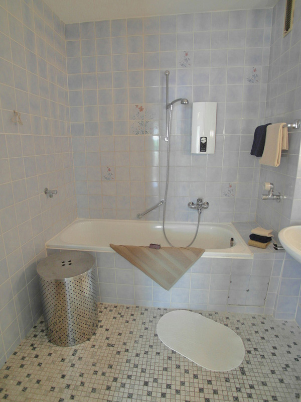 Hellblau gefliestes Bad mit schwarz-weißem Mosaikfliesen-Boden