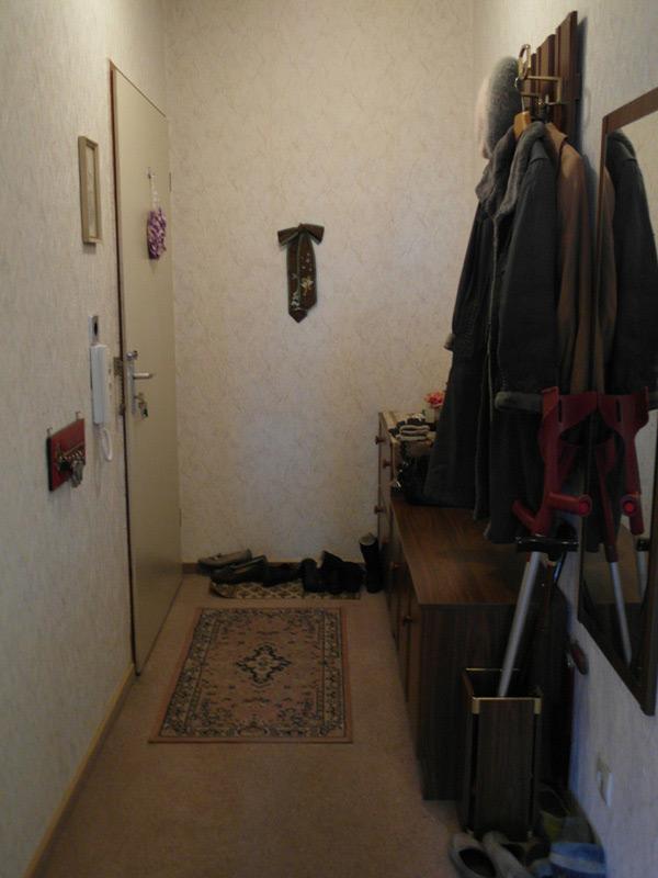 Altmodischer Flur mit voller Garderobe und einem Orientteppich