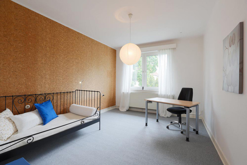 Weißes Zimmer mit einem Bett, Stuhl und Schreibtisch und einer Korkwand