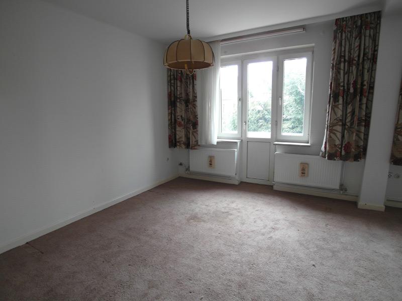 Weißes, leeres Zimmer mit grauem Fußboden und einer Fenstertür
