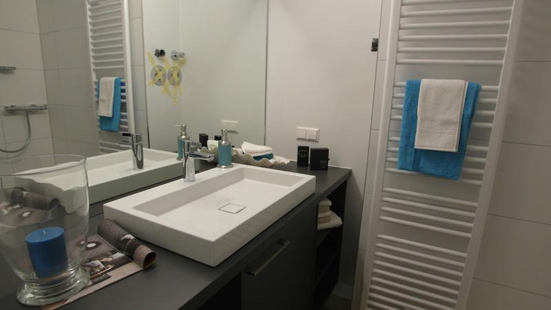 Weißer Waschtisch vor einem großen Spiegel