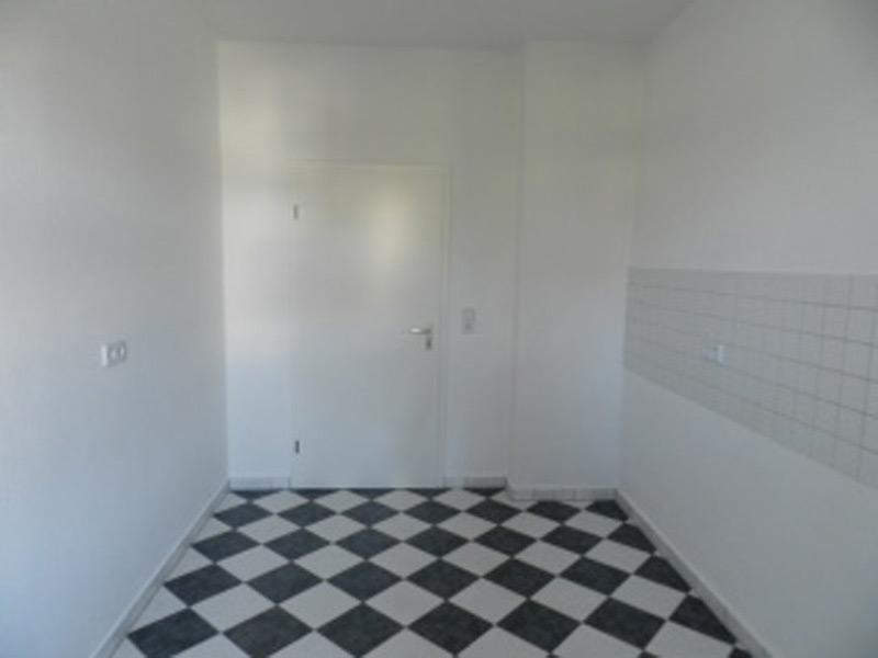 Leere, weiße Küche mit einem Schachbrettboden