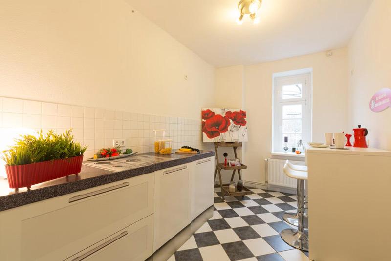 Schmale, weiße Küche mit roten Akzenten