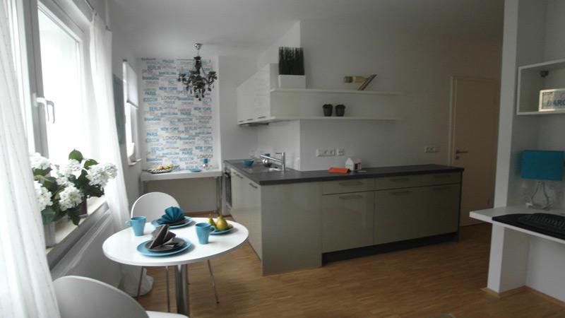 Weiße Küche mit Laminatboden und einer grauen Küchenzeile