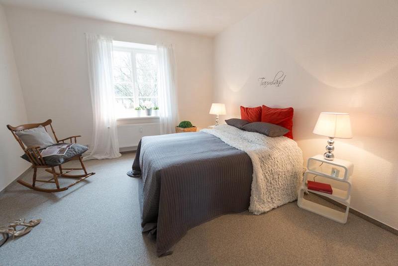 Weißes, geräumiges Schlafzimmer mit einem Doppelbett und einem trendy Wandtattoo