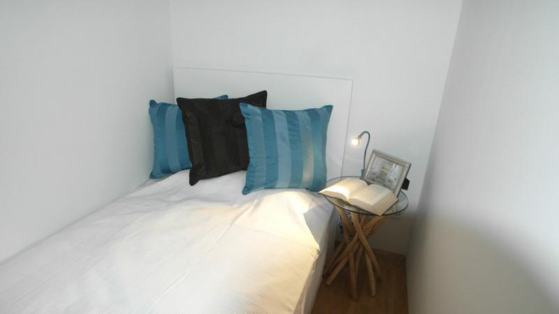 Kompaktes, gemütliches Schlafzimmer mit einem Nachttisch mit einer Glas-Tischplatte