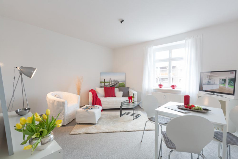 Weißes Wohnzimmer mit hellgrauem Teppich und Akzenten in Rot und Gelb