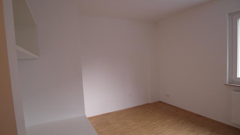 Weißes, leeres Zimmer mit einem Laminatboden