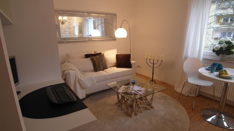 Weißes Wohnzimmer mit einem Laminatboden und weißem Mobiliar