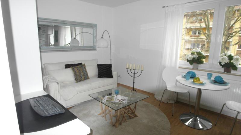 Weißes Wohnzimmer mit einem Glastisch und Laminatboden