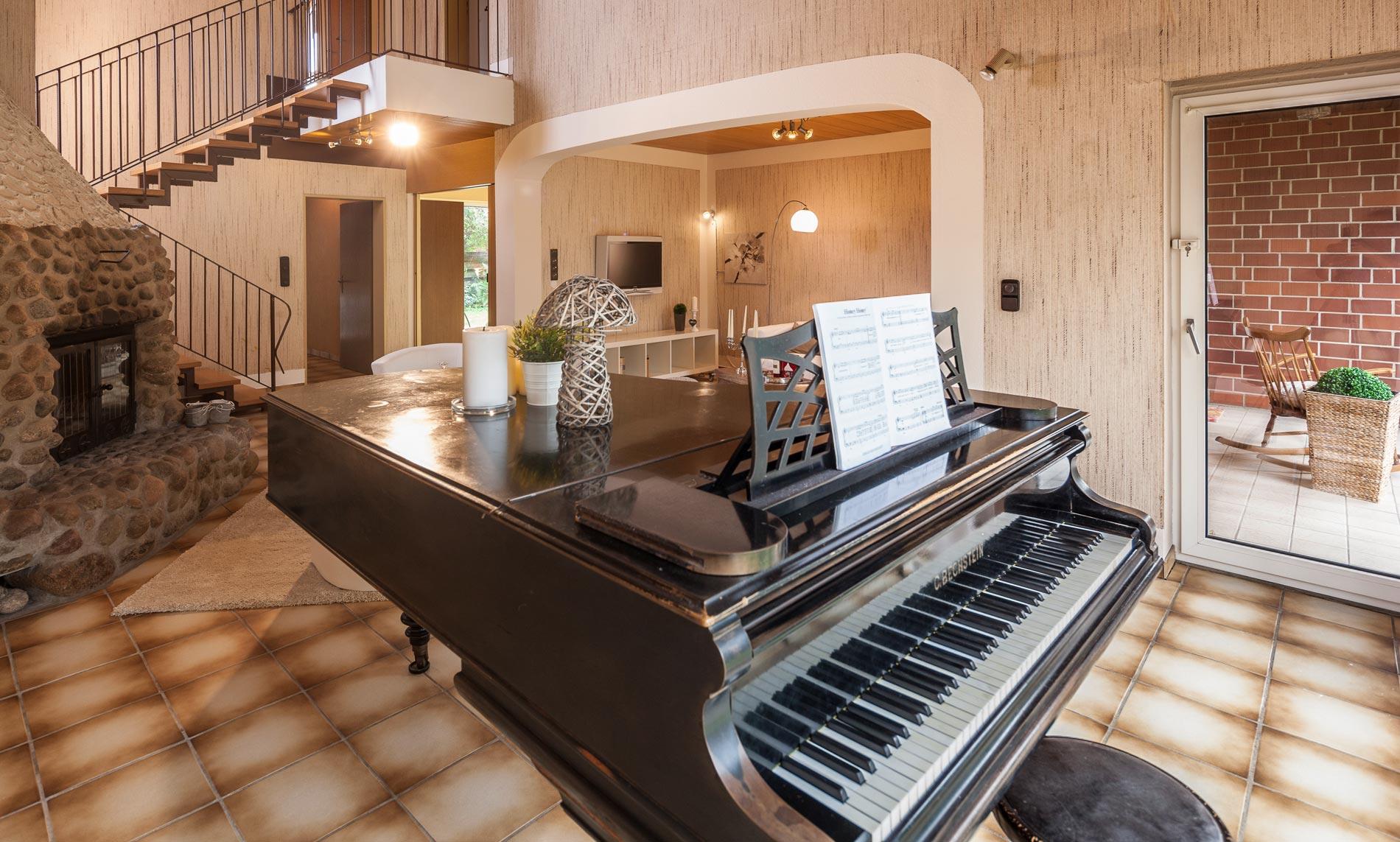Wohnzimmer mit einem Piano vor der Fensterfront