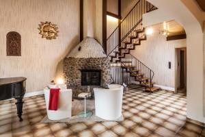 Rustikales Wohnzimmer mit einem Piano und einem massiven Ofen aus Naturstein