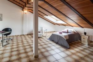 Schlafzimmer mit einer Dachschräge mit Holzfurnier