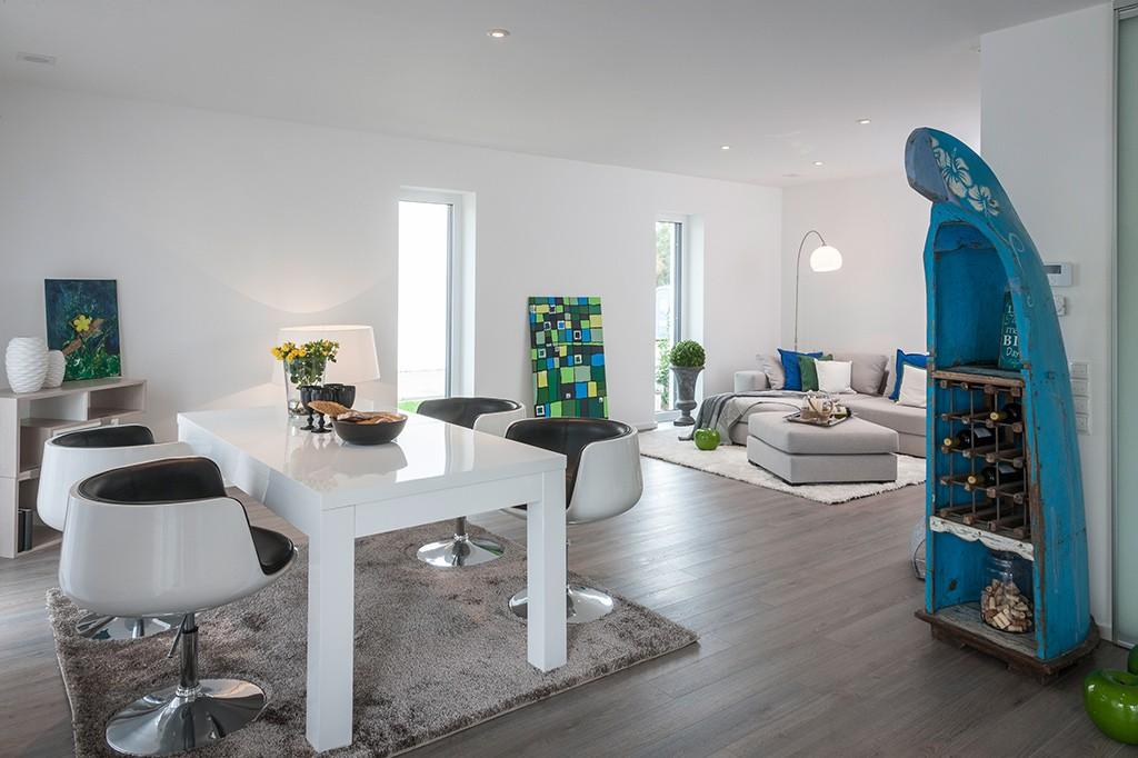 Geräumiges, weißes Ess-und Wohnzimmer mit dunklem Holzboden