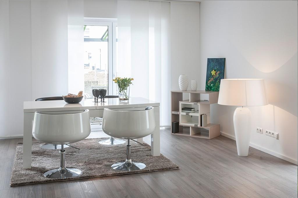 Sauberes, modernes Esszimmer mit weißen Wänden und Holzboden