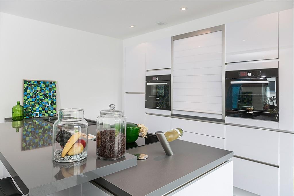 Moderne Küche mit grauer Arbeitsfläche und weißem hochglanz Mobiliar