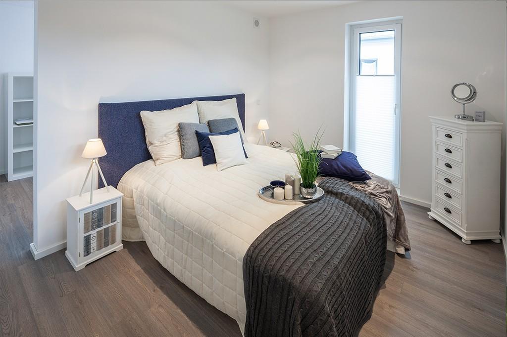 Schlafzimmer mit einem Doppelbett hinter einer Trennwand